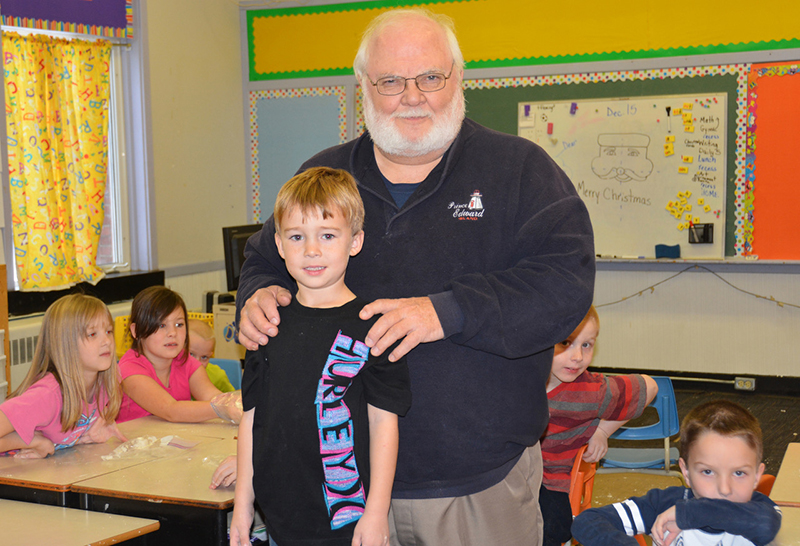 Gordon Porter and little boy smile at the camera in classroom.
