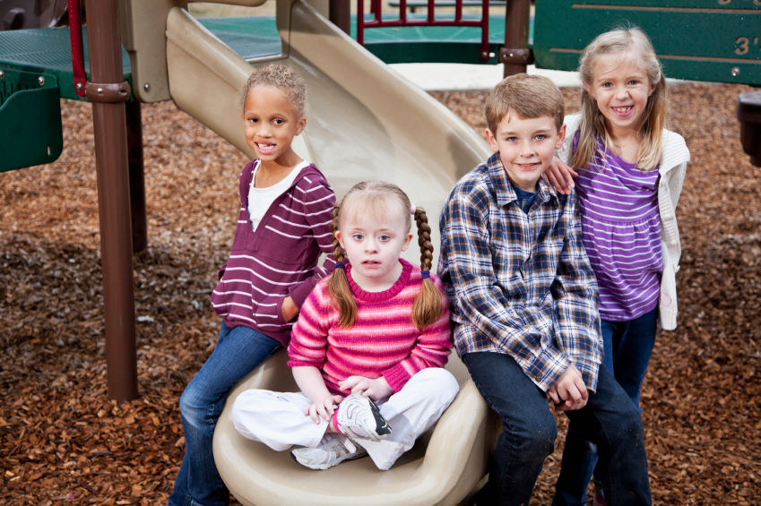 Multi-ethnic group of children on playground, ages 7 to 9. Girl sitting on slide has down syndrome.